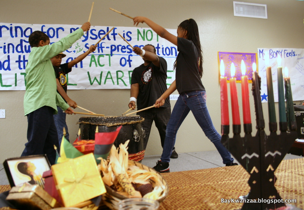 A group performs an African drum song during a Kwanzaa celebration